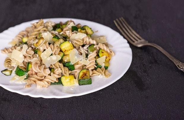 макароны с овощами на тарелке, рядом вилка