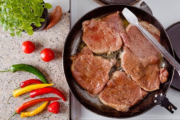 отбитые кусочки свинины на сковороде, цветной перец и зелень