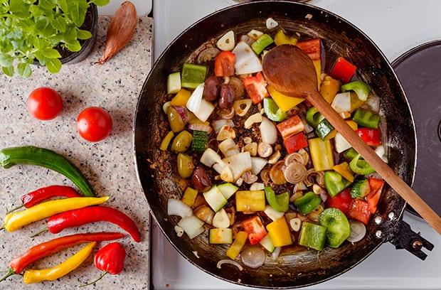 нарезанный цветной перец с луком и лопаткой на сковороде