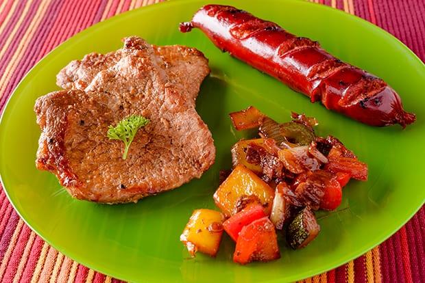 жареная отбивная с овощами и сосиской на зеленой тарелке