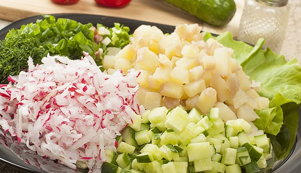 нарезанная картошка с огурцами и тертой редиской в миске