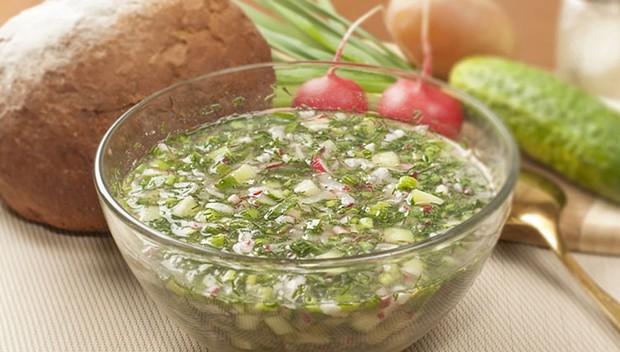 овощная окрошка с зеленью в тарелочке, рядом ложка
