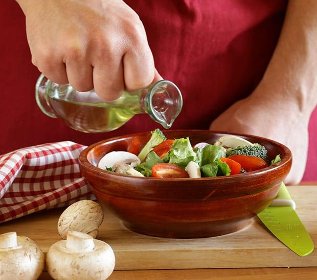оливковое масло вливается в мисочку с овощами