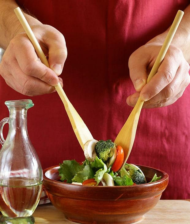 овощной салат в мисочке перемешивается двумя лопатками