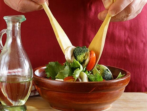 овощной салат с грибами в мисочке, оливковое масло в графине