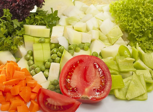 нарезанные перец, кабачки, помидоры, морковь, зеленый горошек и зелень
