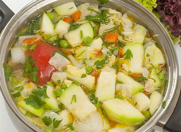 нарезанные кабачки, помидоры, перец и зелень с водой в кастрюле