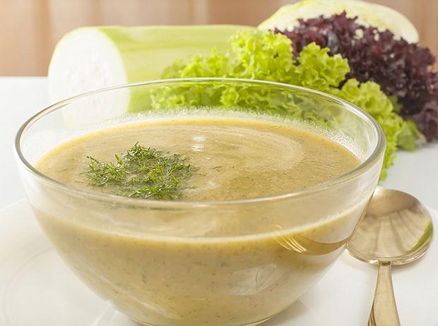овощной суп-пюре с зеленью в тарелке, рядом ложка
