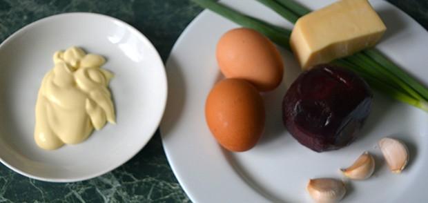 яйца, свекла, сыр, чеснок и зеленый лук на тарелке