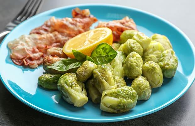 брюссельская капуста с беконом, лимоном и зеленью на тарелке