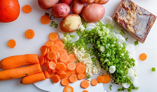 нарезанные морковь и зеленый лук, картошка и бекон