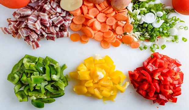 нарезанный цветной перец, морковь, зелень, бекон и картошка