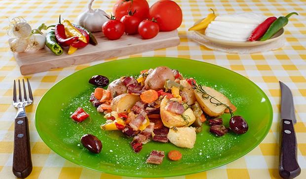бекон с овощами на тарелке. рядом вилка и нож