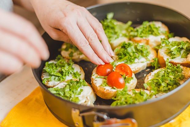 половинки помидоров выкладываются на хлеб с рукколой