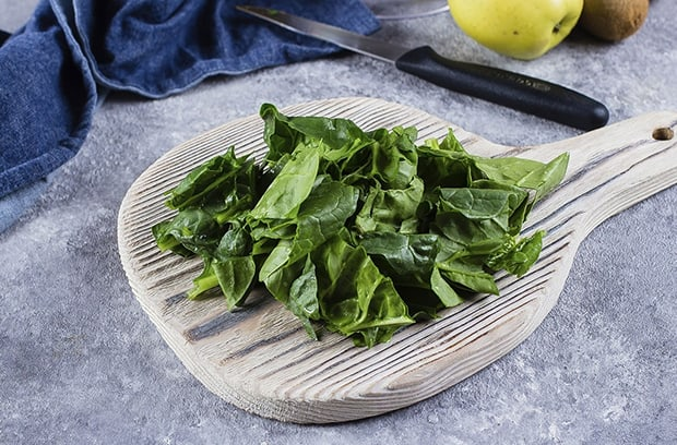 порванные листья шпината на доске