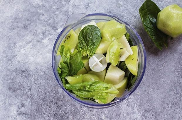 кусочки киви яблок и шпината в чаше блендера