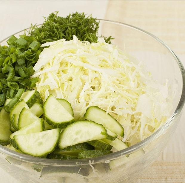 нарезанные огурцы, капуста и зелень в тарелке