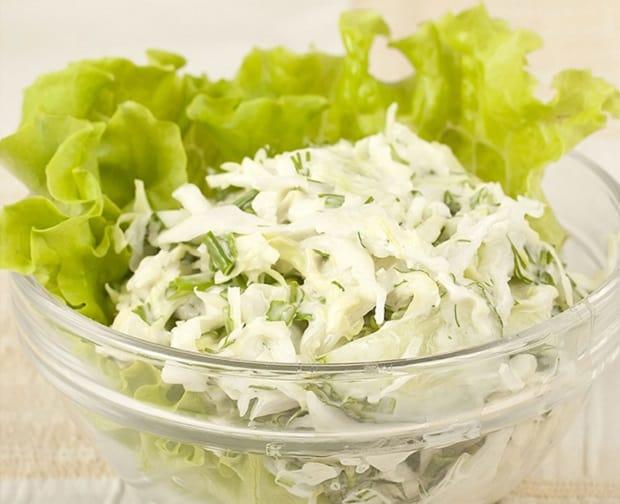 капустный салат с огурцами и зеленью в тарелке