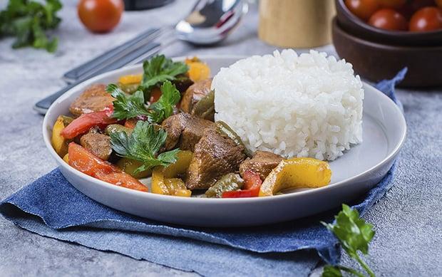тушеные куриные грудки с овощами и рисом на тарелке