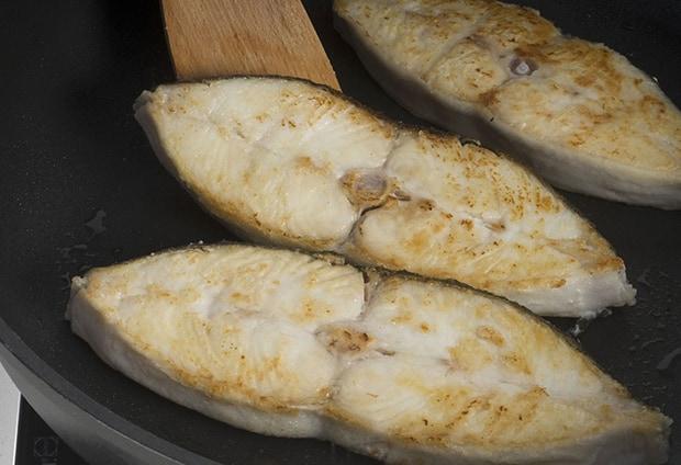 три жареных стейка палтуса на сковороде