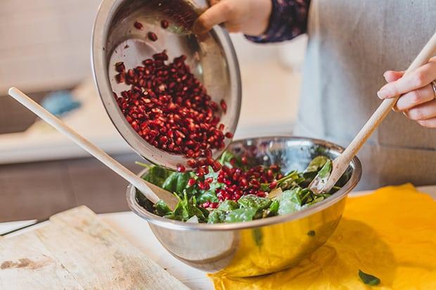 зерна граната высыпаются в миску со шпинатом