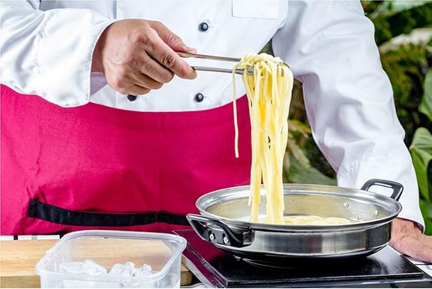 отварные спагетти извлекаются из кастрюли