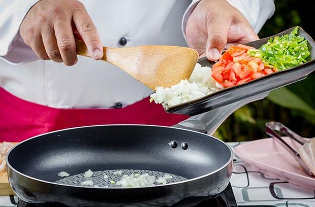 нарезанный лук высыпается на сковороду