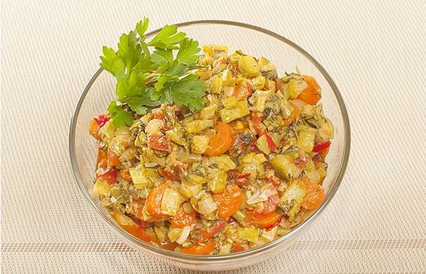 тушеные кабачки с помидорами, морковью и зеленью в тарелке