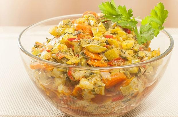 тушеные кабачки с помидорами и зеленью в тарелке